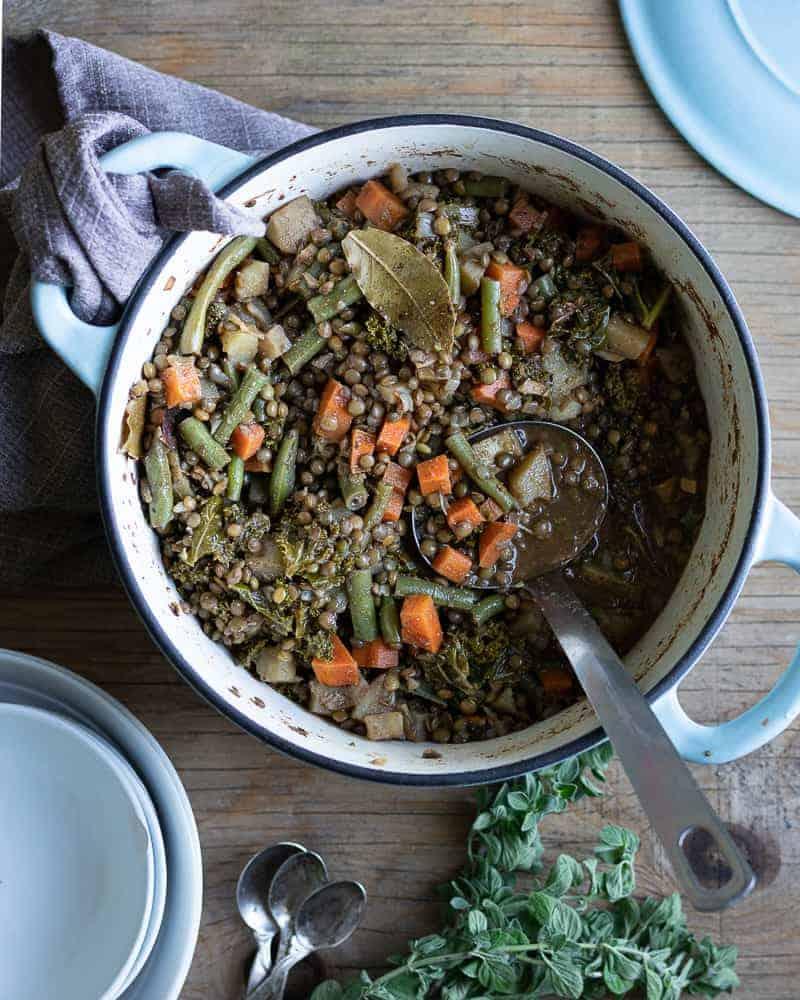 meal prep pot of lentil stew sitting on a wodden table