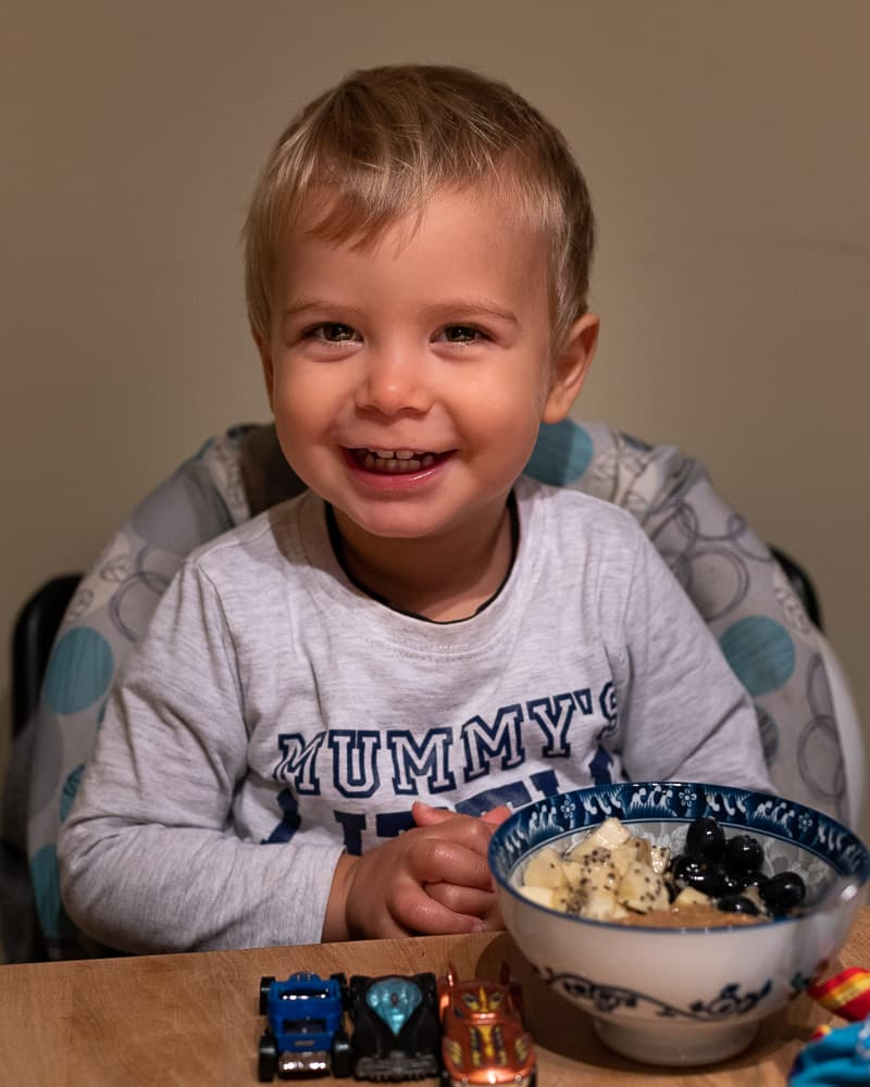 toddler sitting at the table eating a bowl of oatmeal