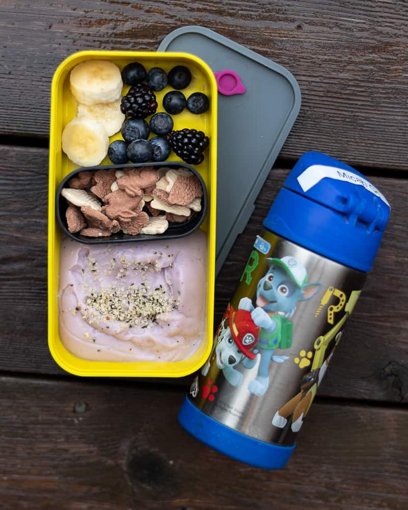 Bento box full of yogurt, crackers and fruit with a water bottle