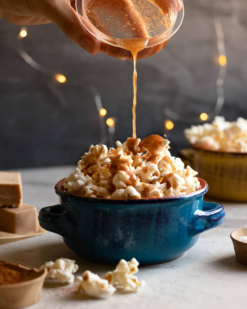 cinnamon spiced butter being poured onto popcorn in a blue bowl with twinkly lights in the background