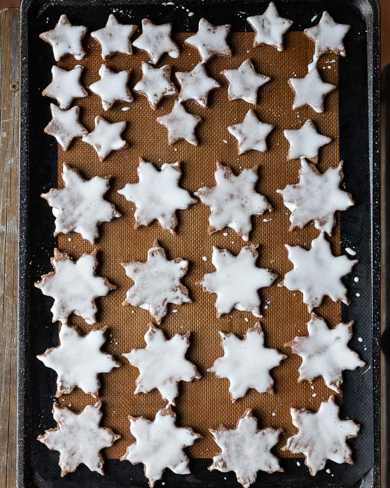 cookie stars on a baking sheet covered with frosting