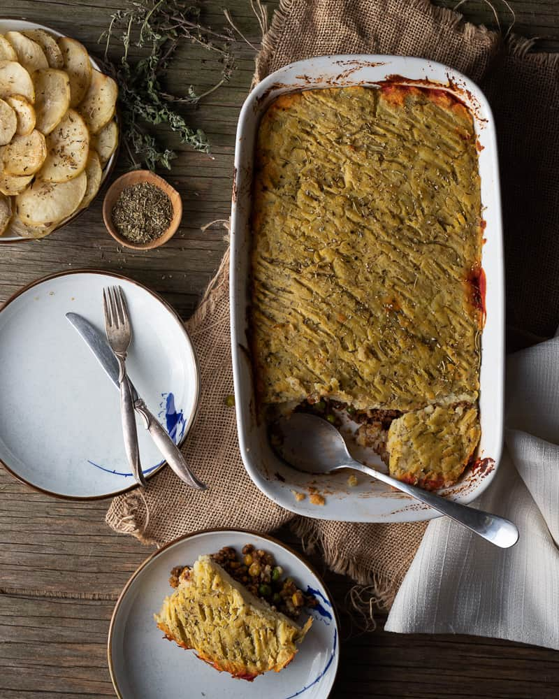 overview of vegan shepherd pie with plates and roasted potatoes around