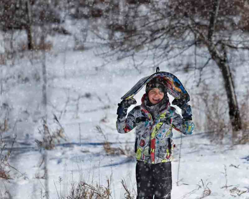 child holding a sled as it snows around him