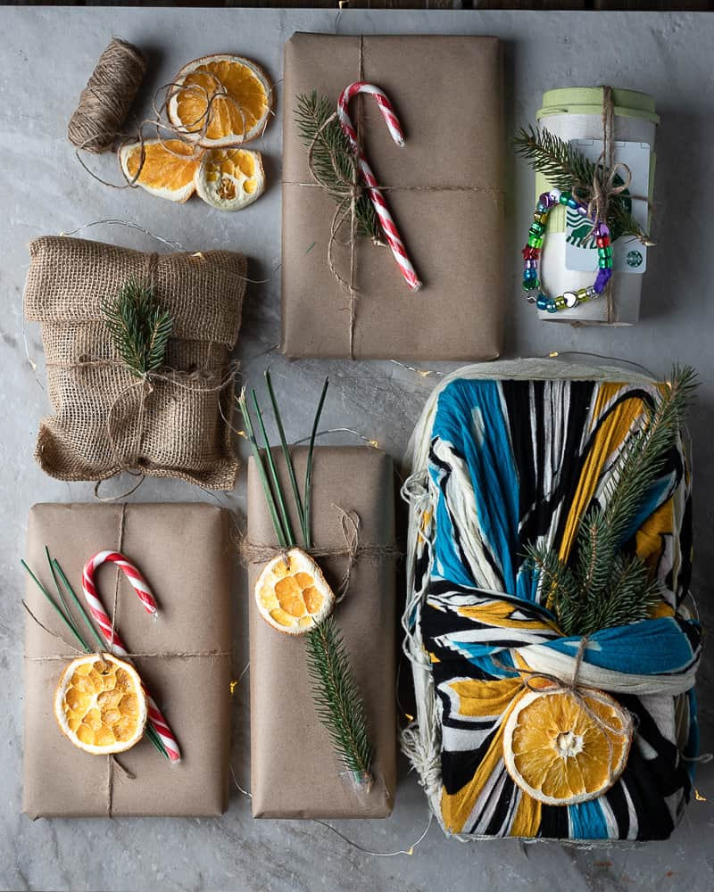 Eco-friendly wrapped presents decorated with candy canes and dried fruit on a marble table