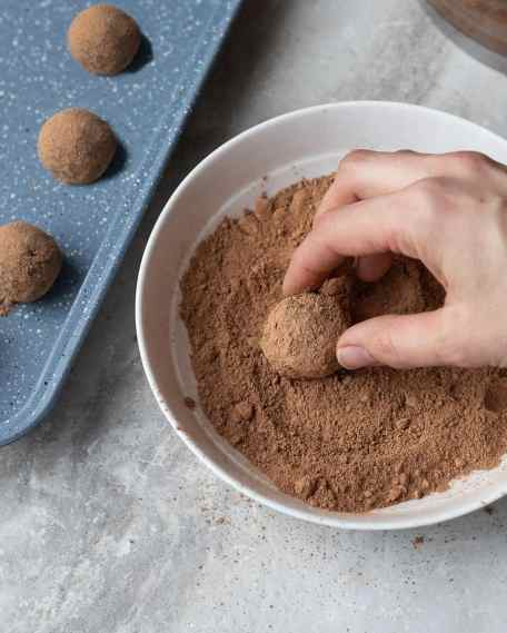 No bake energy bites being rolled in cocoa powder