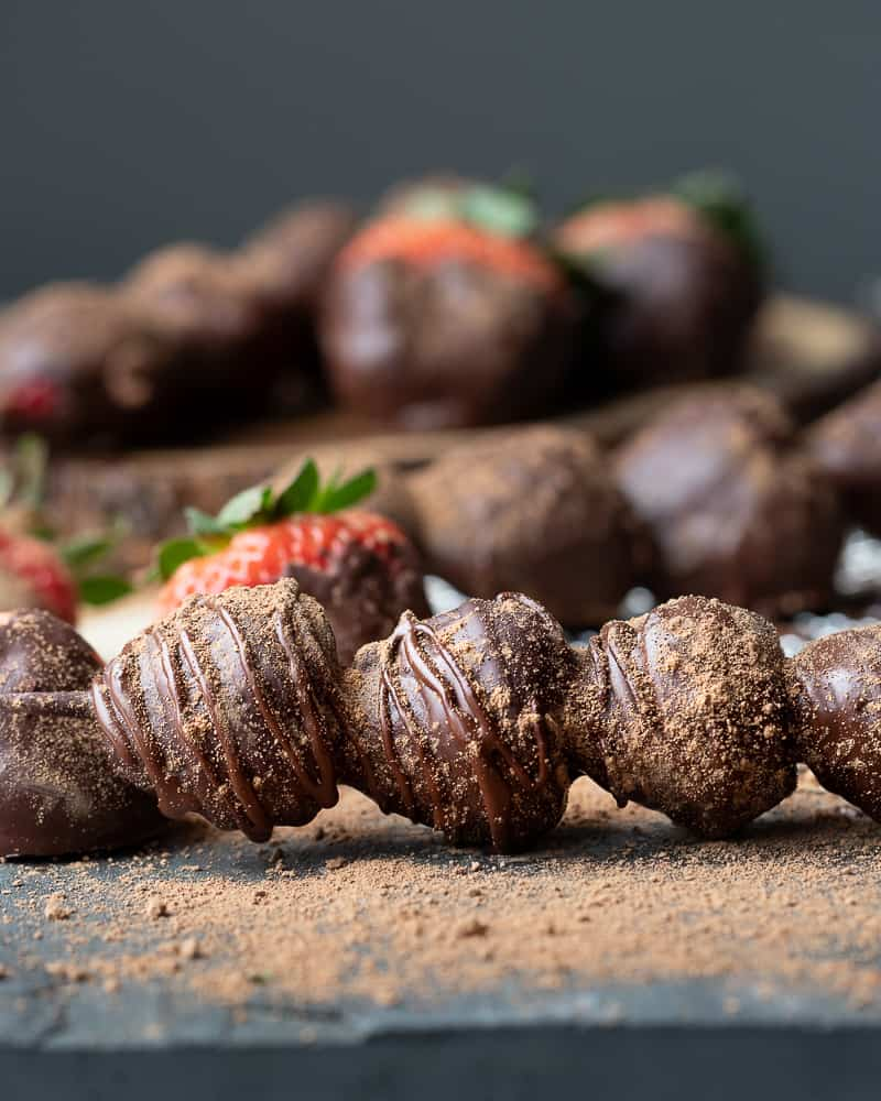 Straight view of chocolate covered strawberries on a stick with strawberries in the background