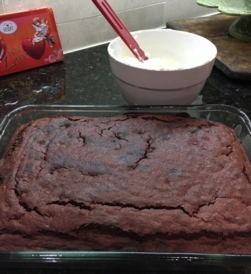 Baked Red Velvet Brownies with bowl of prepared Cream Cheese Frosting