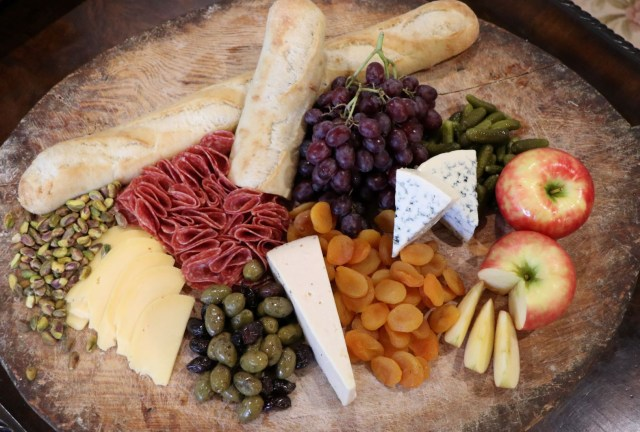 Cheese and other foods on a wooden board.