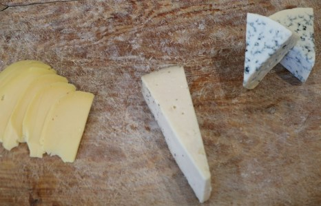 3 types of cheese on a wooden board.