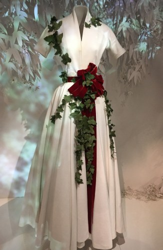 Cream colored Dior gown with red velvet ribbon and ivy.