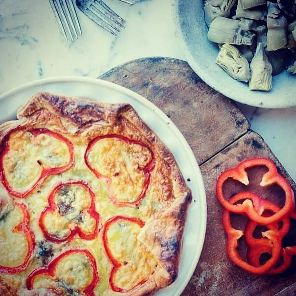 Artichoke and red Pepper Quiche on a wooden board.