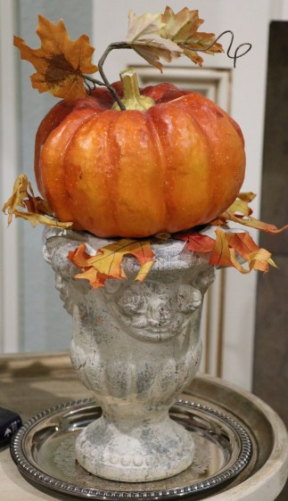 Pumpkin and leaves in an urn.