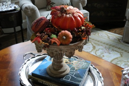 Pumpkins arranged on a pedestal.
