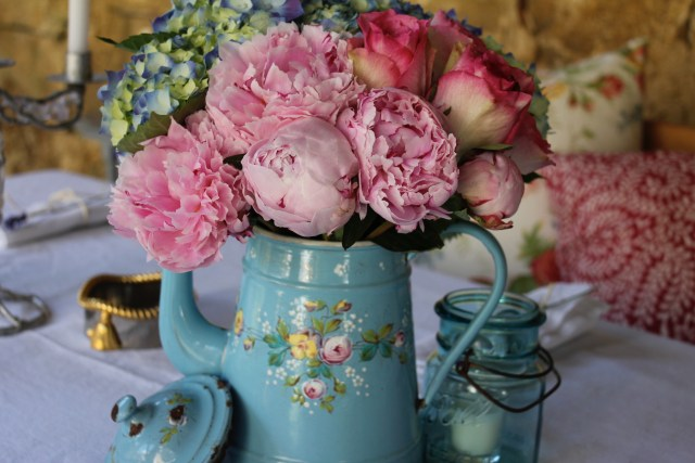 Vintage metal flower pot with pink and blue flowers.