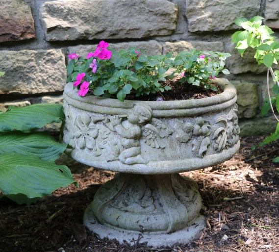 Cherub birdbath with pink impatience blooming.