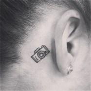 Black And White Cute Camera Tattoo On Back Ear http://www.tattooshunt.com/black-and-white-cute-camera-tattoo-on-back-ear/