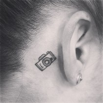 Black And White Cute Camera Tattoo On Back Ear http://www.tattooshunt.com/black-and-white-cute-camera-tattoo-on-back-ear/