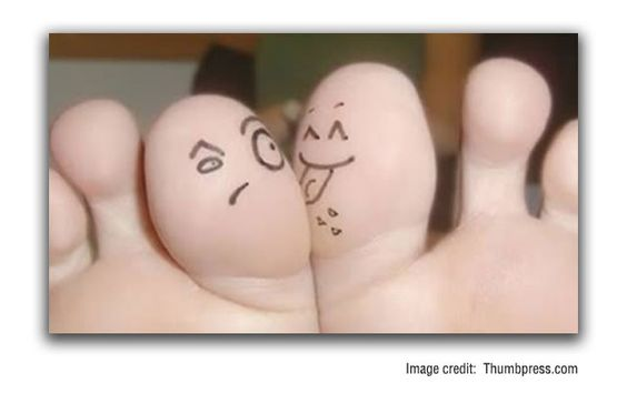 Funny smiley face under toe tattoo