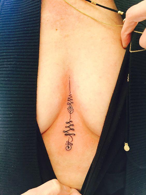 Unique unalome tattoo between breasts