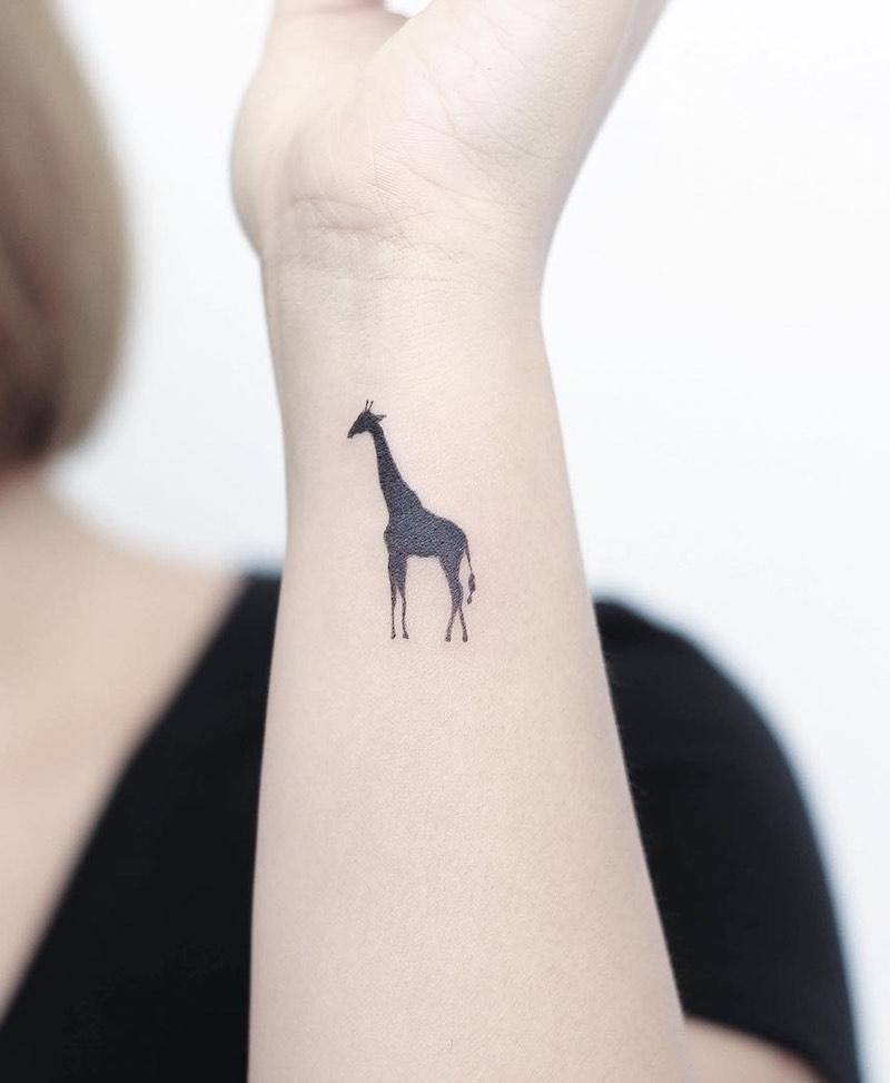 Small giraffe tattoo on wrist