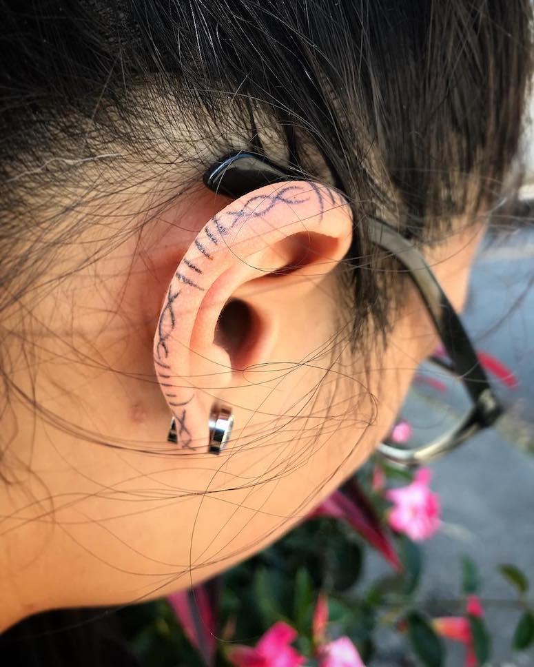 Different lines tattoo on ear lobe