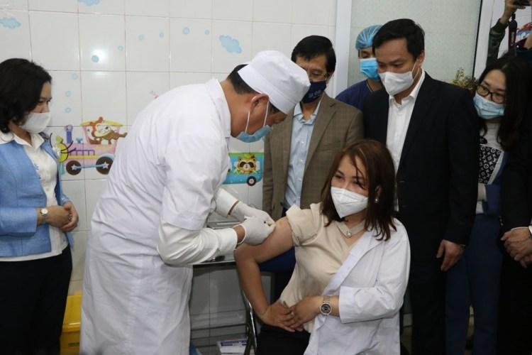 El viceministro vietnamita de Salud Do Xuan Tuyen realiza directamente la vacunación contra COVID-19 para una médica de la provincia de Hai Duong (Foto: VNA)