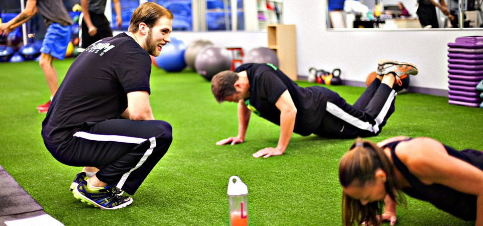 Alex training two clients doing pushups.