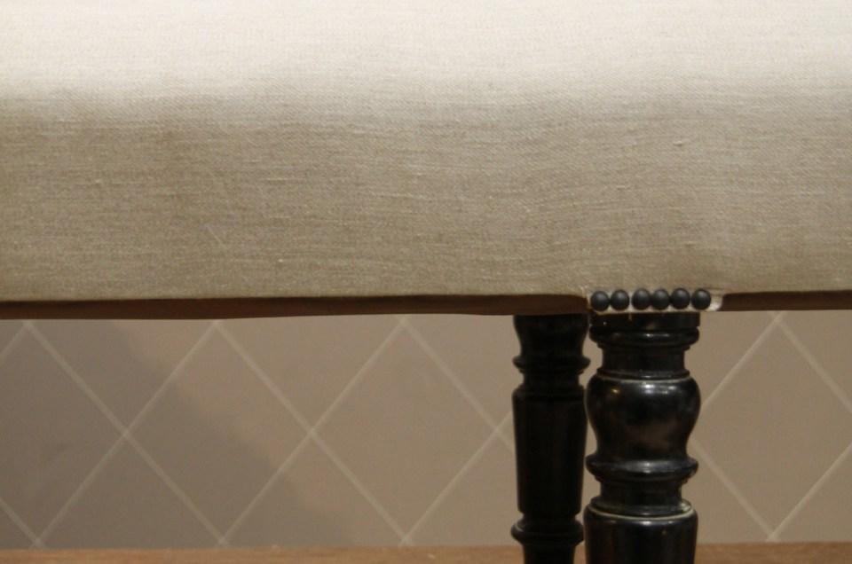 Longue banquette Napoléon III en toile grise, finition clous décoratifs noir mat