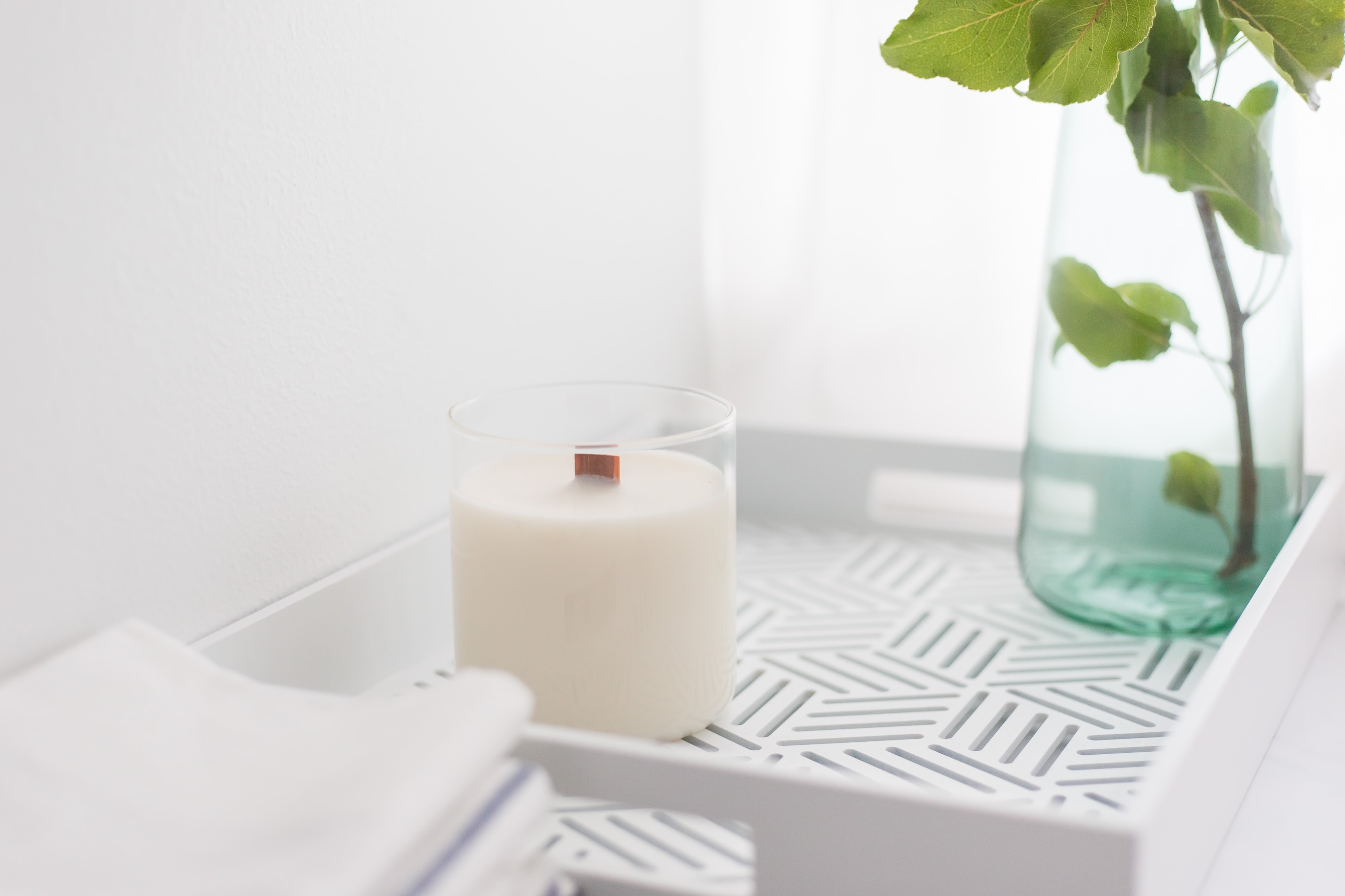 White candle on a white tray with a teal vase sitting next to it
