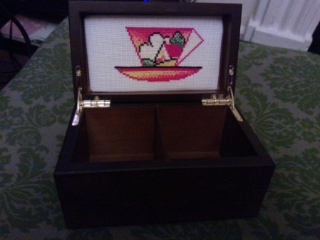 Embroidery padded and mounted in a Twinings tea caddy