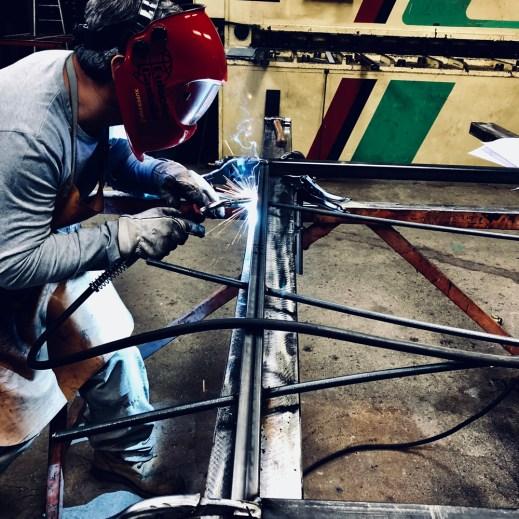 Soudure de barreaux sur un portail acier dans l'atelier de métallerie