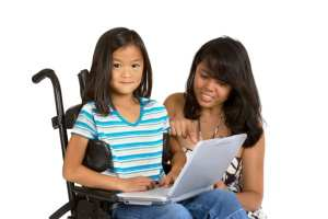 This is a photo of a girl in a wheelchair with a laptop. Her mother is looking at the screen with her.