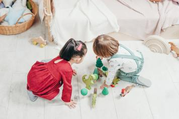 Two kids playing with toys on the floor