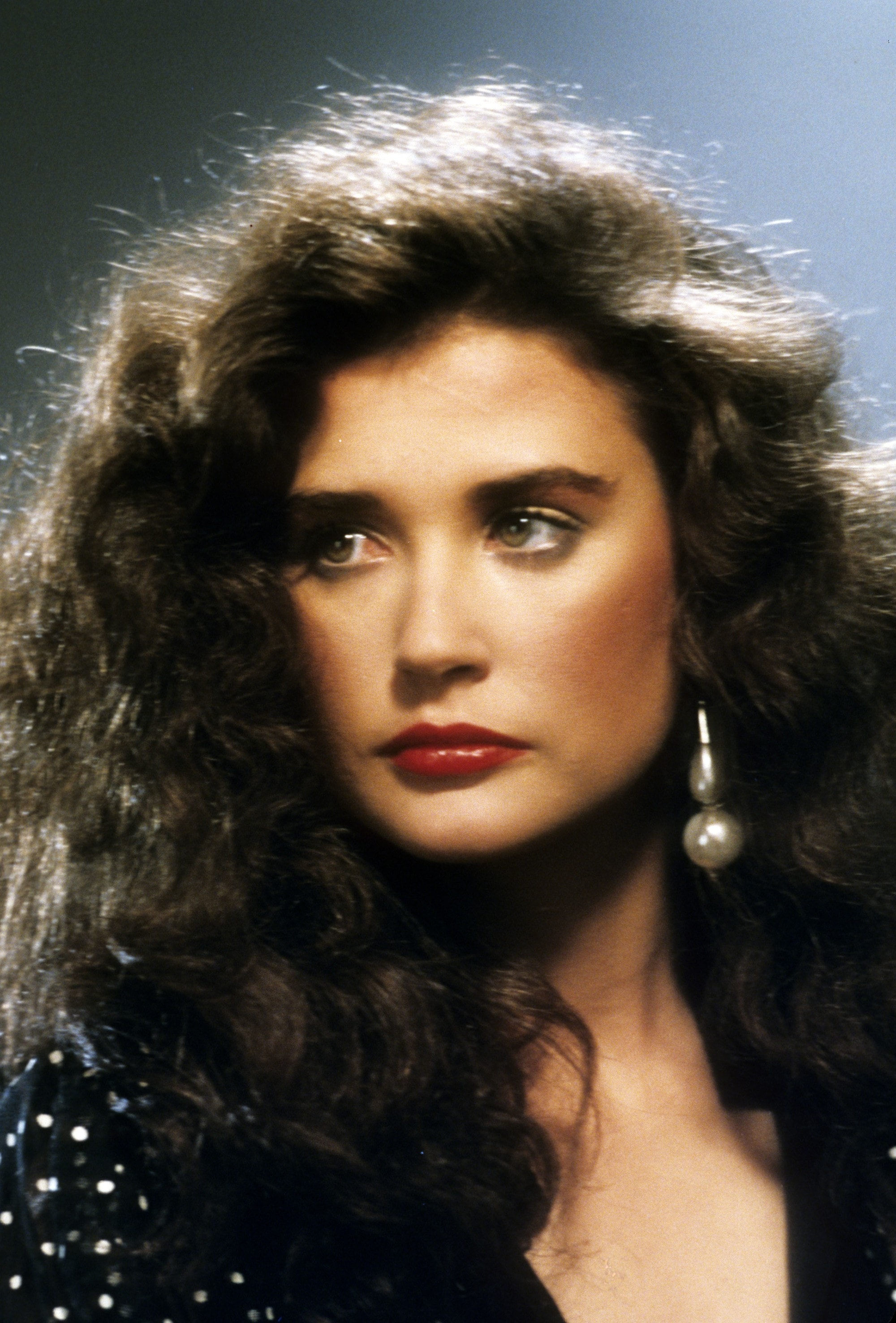 23 awesome  80s hairstyles that are making a comeback 80s hairstyles  Young Demi Moore with brown curly wavy big  80s hair  wearing a