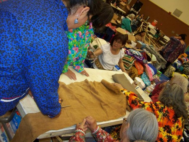 My relatives are cutting a moose hide at a potlatch during the giveaway. Photo by Angela Gonzalez