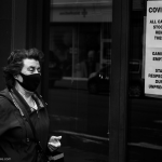 a woman with grey hair walks by a business shut by COVID-19 restrictions