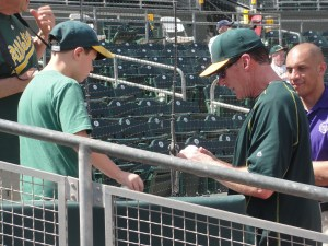 After signing a ball for a young fan on Sunday, A's manager Bob Melvin then broke the bad news that he was being reassigned to the minor league camp.