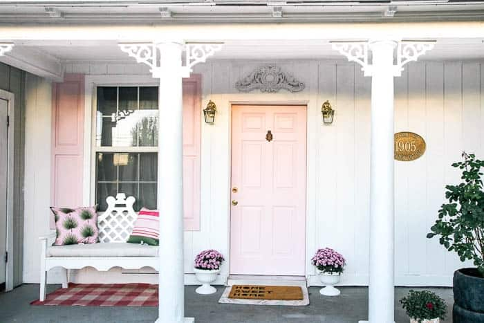 Welcome to my front porch. My house is a 1905 Victorian and I tried to reflect that with the decorating of this small area. I share ideas for how to DIY your own front porch to makeover perfection. The perfect porch remodel includes columns, plants, furniture, brass lanterns, a pineapple knocker, decorative trim and pink shutters and door.