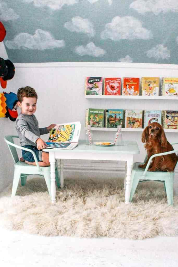 Don's toy story room reveal. A vintage inspire boys room full of car art and blue clouds on the walls. Ready for some vintage modern decor ideas? I share some affordable DIYS including an IKEA hack bookshelves and a ceiling with the cutest fan