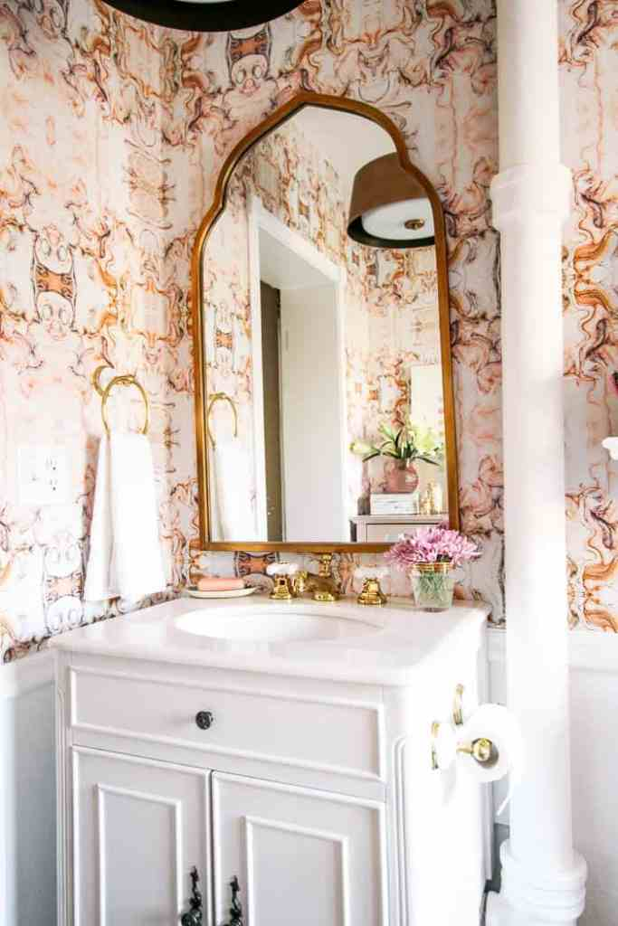 Bathroom Reveal! Check out this beautiful DIY bathroom with pink abstract marble wallpaper, brass accents, an arch mirror, stone vanity, clawfoot tub. It's a modern glam decor dream!