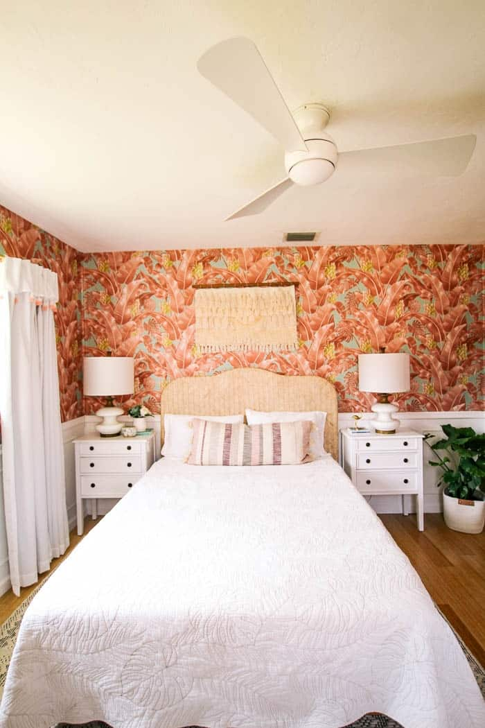 pink master bedroom reveal. Ready for a before and after for this small room makeover that was done on a budget?! It's modern and cozy while having a colorful design. There's wall decor over the bed with white bedding. It's cute with a bit of a boho coastal vibe.
