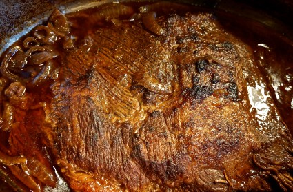 On stovetop, heat oil in bottom of Dutch oven and brown brisket on both sides, starting wtih fat side down. This will take approximately 5 minutes per side.