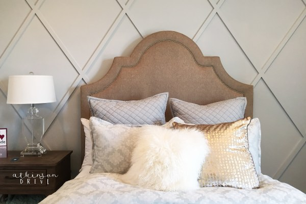Beautiful bedroom design with a nailhead-tril headboard and a simple wood accent wall.