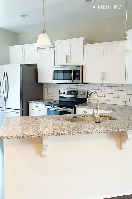 New Home: This light and bright kitchen is outfitted with white shaker-style cabinets, black and white granite, and white subway tile with dark grout