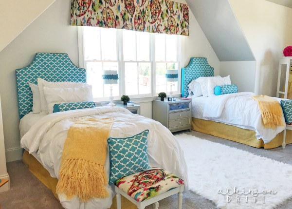 Shared girls' bedroom in bright white with pops of color featuring a shiplap accent wall /// Woodridge Parade of Homes Tour by Atkinson Drive