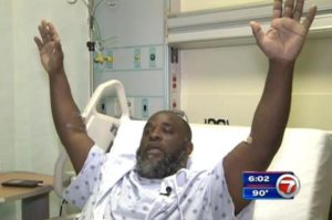 Charles Kinsey, 41, demonstrates how he had his hands in the air shortly before he was shot by police. Image courtesy of ABC 7.