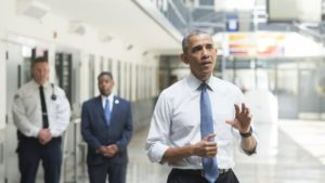 President Obama speaks as Charles Samuels (C), Bureau of Prisons Director, and Ronald Warlick (L), a correctional officer, look during a tour of the El Reno Federal Correctional Institution in El Reno, Oklahoma, July 16, 2015. Photo by SAUL LOEB/AFP/GETTY IMAGES
