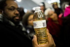 A Pastor holds up a bottle of Flint water during protest in Lansing, Michigan. Photo by Jake May/The Flint Journal