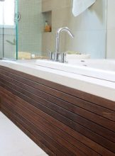 Warm woods can beautifully balance the cool tones that often come with natural stone. Dark South American Ipei wood, milled into custom horizontal bands, complements the light neutrals in this bath, including sparkling chrome fixtures and expanses of Venetino marble. Terracotta Properties LLC, (404) 377-0906