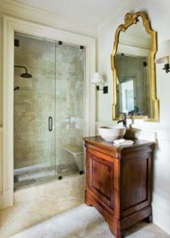 A harmonious union of contemporary and traditional styles all but guarantees a truly timeless space. In this case, a chic travertine bowl sink is set upon a classic cherry vanity while the modern stand-up shower is framed by traditional white molding. Even the grand gilt-frame mirror is right at home between a pair of more clean-lined sconces. Robert Brown Interior Design, (404) 917-1333